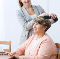 caregiver combing the hair of old woman