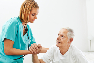 Nurse helping senior men getting up from bed